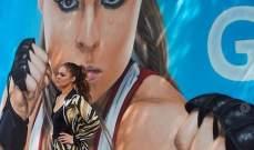 روندا روزي أمام جدارية لها
