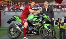 لوكاس بودولسكي يجلس على دراجة نارية في الملعب