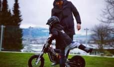 كيمي رايكونين يعلّم إبنه على الدراجة